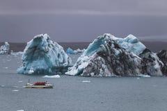 Огромные айсберг и шлюпка resque в Исландии Jokulsarlon стоковые фото