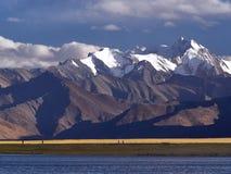 Огромные коричневые горы на береге голубого озера, пики пиков покрыты с вечными снегами и ледниками, вечером на озере t Стоковые Изображения RF
