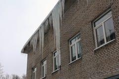 Огромные сосульки на крыше здания Стоковое Изображение