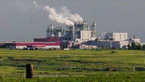 Огромный конкретный завод с трубами среди полей сток-видео