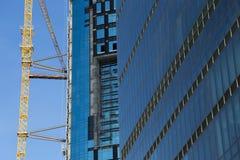 Огромный кран поднимая около конструкции небоскреба против голубого неба в Стамбуле Стоковая Фотография RF