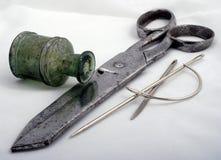 Огромный старый стальной серый цвет для портноя scissors лежать раскосно на белой предпосылке, к праву 3 толстых выведенной иглы  Стоковое фото RF