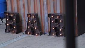 Огромный b, a, r коричневеет металлические письма с несколькими оранжевых лампочек установленных к нему акции видеоматериалы