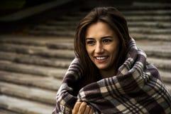 Оглушая усмехаясь девушка обернутая в одеяле Стоковое Изображение RF
