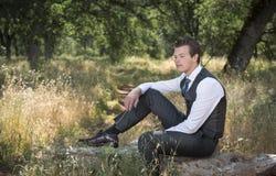Одеванный молодой человек сидя вне ослаблять стоковые фотографии rf