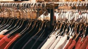 Одежда большое количество женщин видов других цветов на вешалках и лож на полках в магазине одежды  сток-видео