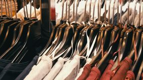 Одежда большое количество женщин видов других цветов на вешалках и лож на полках в магазине одежды  видеоматериал