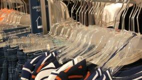 Одежда и джинсы различных пестротканых женщин вися на вешалках в магазине одежды в торговом центре или торговом центре сток-видео