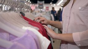 Одежда моды женщины Shopaholics отборная новая на вешалках в магазине во время скидок продаж, рук на несосредоточенной предпосылк видеоматериал