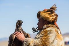 Одежда охотника орла казаха традиционная, пока охотящся к зайцам держа беркута на его руке Стоковая Фотография RF