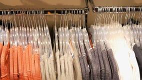 Одежда различных пестротканых женщин вися на вешалках в магазине одежды в торговом центре или торговом центре видеоматериал