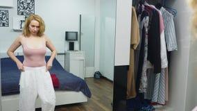 Одежда, шкаф, мода, стиль и концепция людей озадаченная блондинка делает выбор из одежд, стоя около акции видеоматериалы