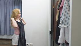 Одежда, шкаф, мода, стиль и концепция людей озадаченная блондинка делает выбор из одежд, стоя около сток-видео