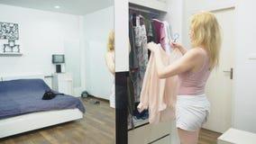 Одежда, шкаф, мода, стиль и концепция людей озадаченная блондинка делает выбор из одежд, стоя около видеоматериал