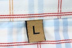 одежда l размер макроса ярлыка реальный Стоковая Фотография RF