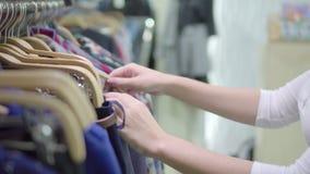 Одежды в магазине Вешалки с платьями Выбор товаров Предпосылка для рекламировать Другие цвета Девушка сток-видео