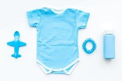 Одежды голубого младенца для мальчика Bodysuit, игрушки, косметики на белом взгляд сверху предпосылки стоковое фото rf