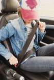 Одежды джинсов девушки битника нося прикрепляют ее ремень безопасности в автомобиле Стоковые Изображения