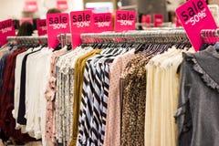 Одежды женщины на вешалке в магазине одежды стоковое изображение rf