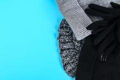 Одежды зимы и осени, шляпы, шарфы, перчатки на голубой пастельной предпосылке Стоковое Фото