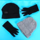 Одежды зимы и осени, шляпы, шарфы, перчатки на голубой пастельной предпосылке Стоковые Изображения