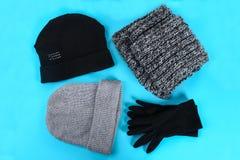 Одежды зимы и осени, шляпы, шарфы, перчатки на голубой пастельной предпосылке Стоковая Фотография