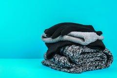 Одежды зимы и осени, шляпы, шарфы, перчатки на голубой пастельной предпосылке Стоковые Фото