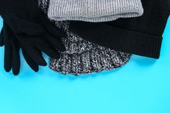 Одежды зимы и осени, шляпы, шарфы, перчатки на голубой пастельной предпосылке Стоковые Фотографии RF