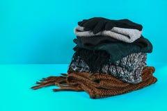 Одежды зимы и осени, шляпы, шарфы, перчатки на голубой пастельной предпосылке Стоковое фото RF