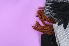 Одежды зимы и осени, шляпы, шарфы, перчатки на фиолетовой пастельной предпосылке стоковые изображения