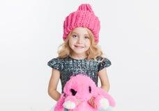 Одежды зимы Портрет маленькой курчавой девушки в связанной розовой шляпе зимы изолированной на белизне Розовая игрушка кролика в  Стоковые Фотографии RF