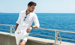 Одежды красивого человека нося белые представляя в пейзаже моря стоковая фотография