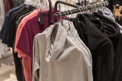 Одежды людей, строка собрания hoodie на вешалке в магазине Стоковые Изображения