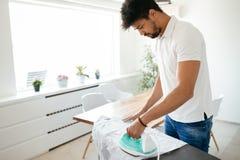 Одежды молодого счастливого человека утюжа Стоковое Фото