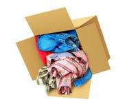 Одежды падают из картонной коробки изолированной на белом backgrou Стоковая Фотография