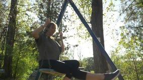 Одежды спорта привлекательной молодой женской модели нося и потеха иметь самостоятельно на качании в природном парке в замедленно акции видеоматериалы