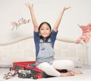 Одежды счастливой милой девушки бросая и сидят на чемодане Стоковые Фотографии RF