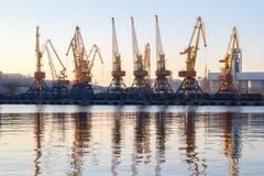 Одесса, Украина - Januadry 02, 2017: Краны в терминале порта груза, краны контейнера груза отразили в воде Заход солнца стоковое изображение rf