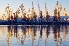 Одесса, Украина - Januadry 02, 2017: Краны в терминале порта груза, краны контейнера груза отразили в воде Заход солнца стоковые фото