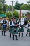 Одетые в форму солдаты и игроки трубы сумки во время парада маршируют Стоковые Изображения