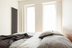 Одеяло и серые подушки на кровати в простом белом интерьере спальни Стоковая Фотография