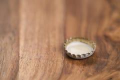 Одиночная белая крышка пивной бутылки на деревянной таблице Стоковые Изображения RF