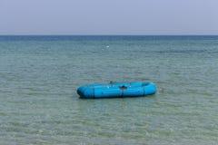 Одиночная голубая резиновая шлюпка в голубом море каникула принципиальной схемы тропическая Изолированный резиновый сосуд Предпос стоковые изображения