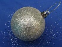 Одиночная шарика рождественской елки серебряная, голубая предпосылка стоковая фотография rf