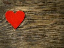 Одиночное яркое красное сердце на backgro темной винтажной текстуры старом деревянном стоковая фотография rf