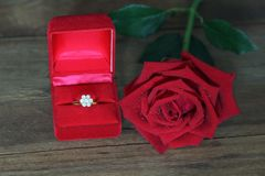 Одиночные красные розы и диаманта обручальное кольцо в красной коробке на деревянной предпосылке стоковые изображения rf