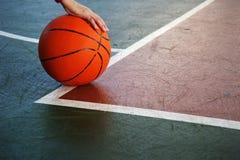 Одиночный оранжевый баскетбол с рукой игрока женщины на зеленом красном spo Стоковая Фотография