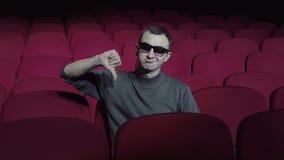 Одиночный человек сидя в удобных красных стульях в темном театре кино и показывая большие пальцы руки вниз сток-видео