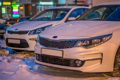 Один белый автомобиль на предпосылке другого запачканного автомобиля в вечере зимы на предпосылке bokeh Стоковое фото RF