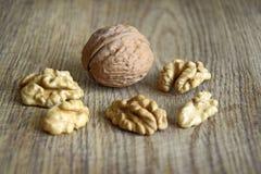 Один весь грецкий орех со стерженями на деревянной предпосылке стоковые фото